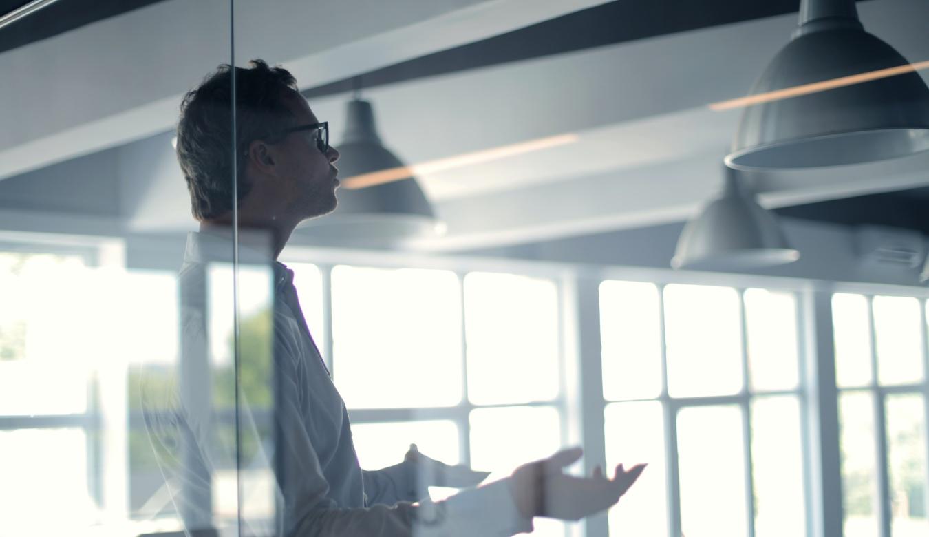 Man in boardroom gesticulating
